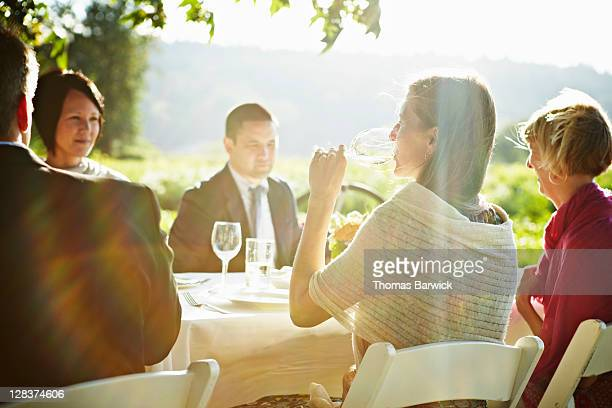 Woman sitting at outdoor table drinking wine