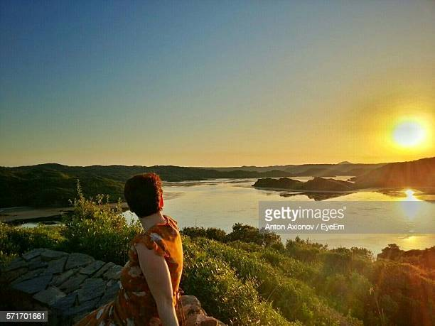 Woman Sitting At Retaining Wall By Lake Against Sky During Sunset