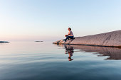 Woman sitting at sea, Sweden