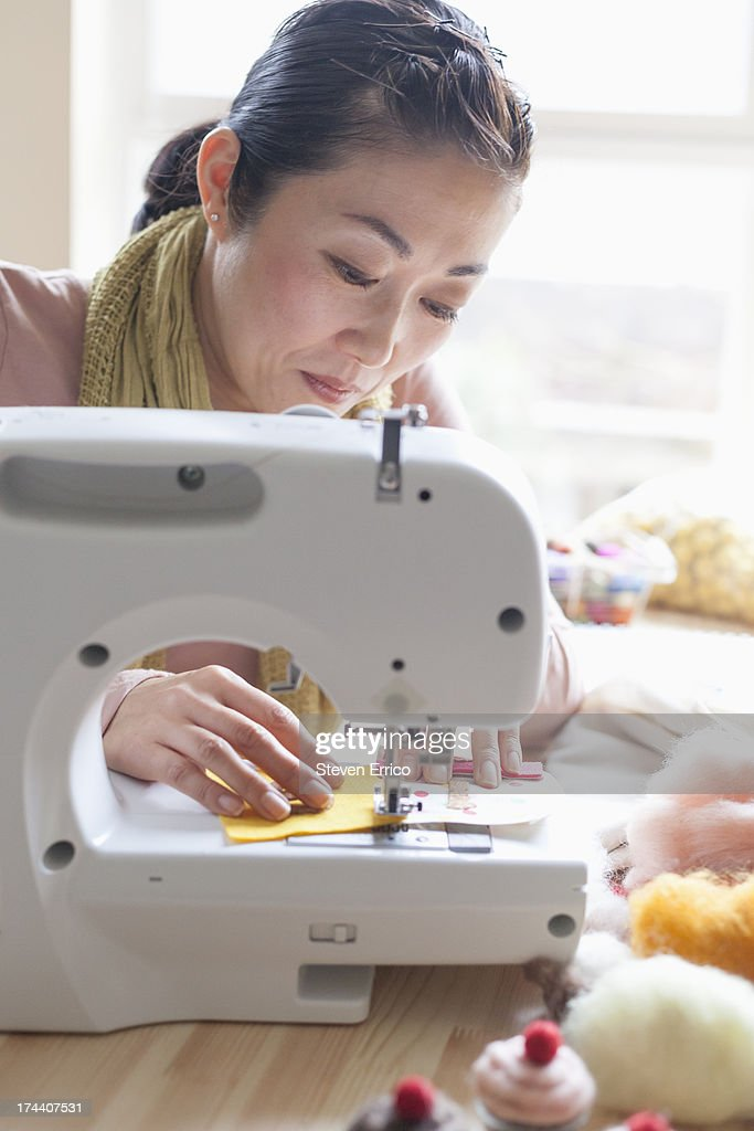 Woman sitting at sewing machine : Stock Photo