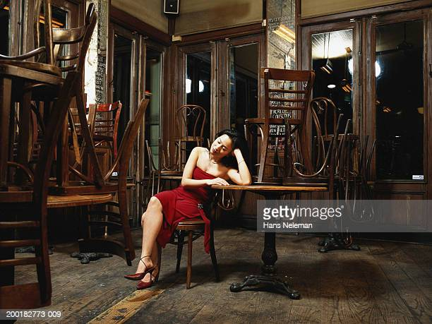 Woman sitting at table in bar closed for night