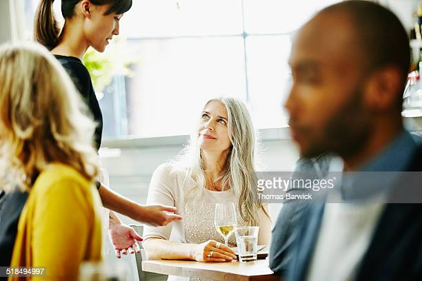 Woman sitting at table in discussion with waitress