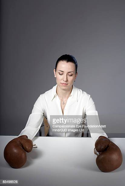 Woman sitting at table wearing boxing gloves