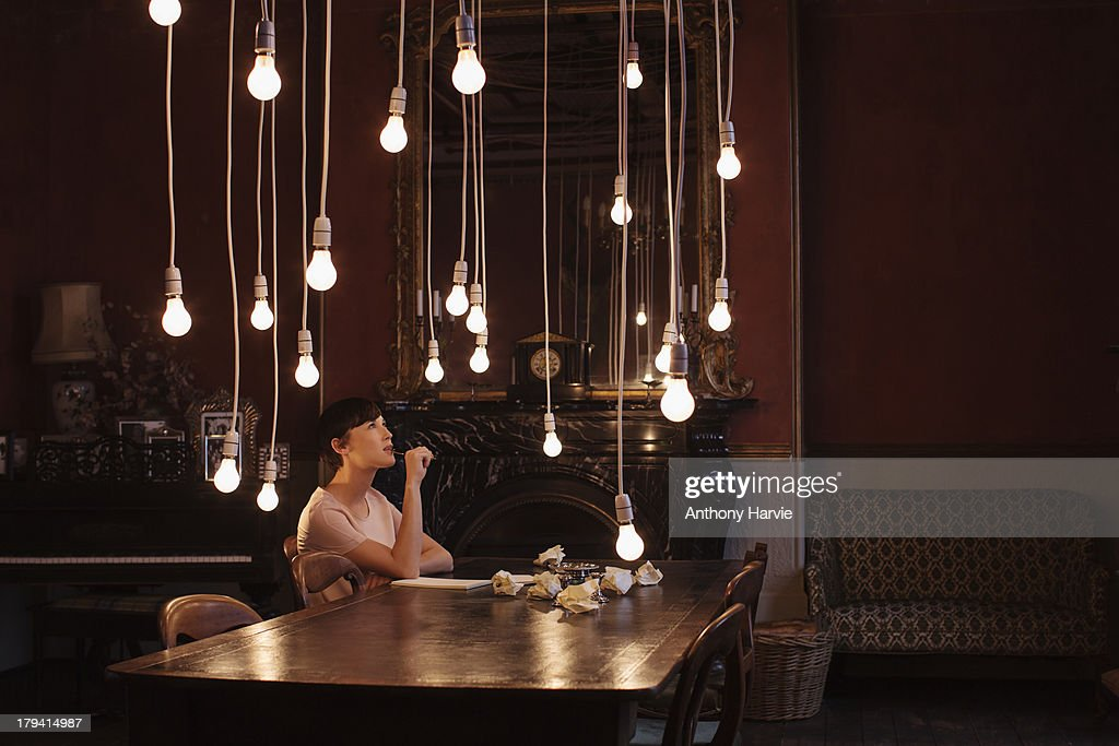 Woman sitting at table with hanging lightbulbs : Stock Photo