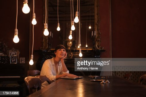 Woman sitting at table with hanging lightbulbs