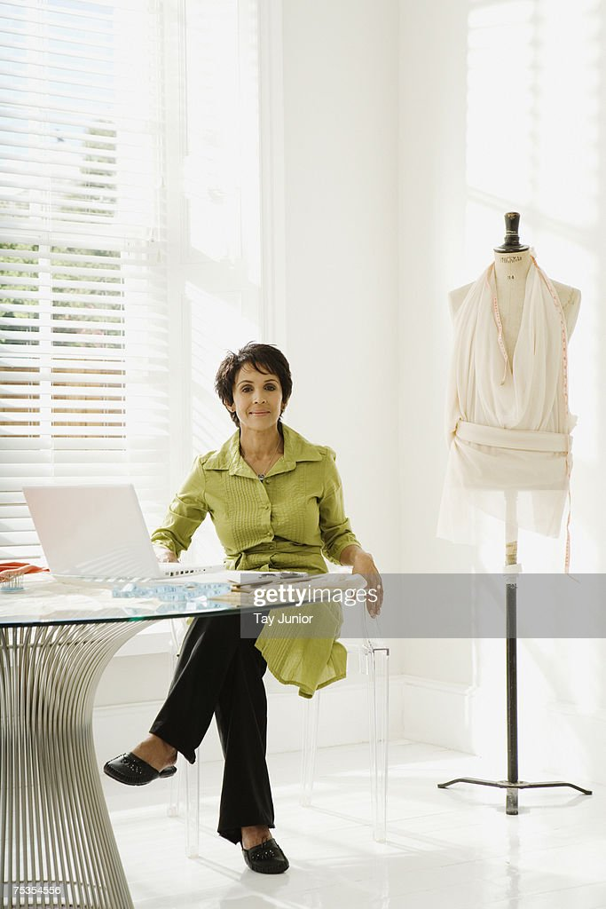 Woman sitting at table with laptop by mannequin, portrait : Stock Photo