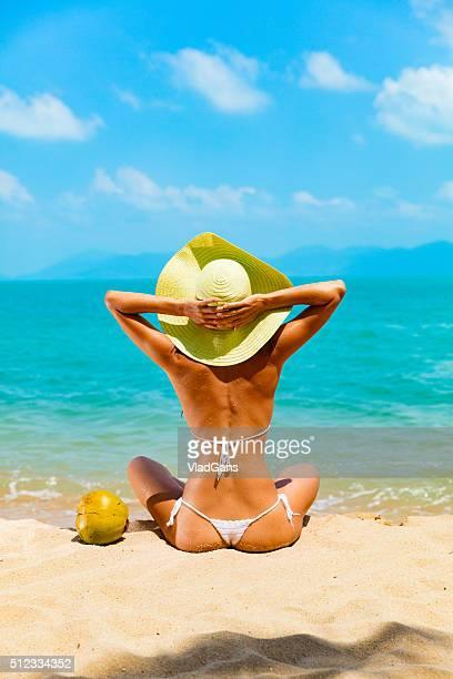 Frau sitzt am tropischen Strand