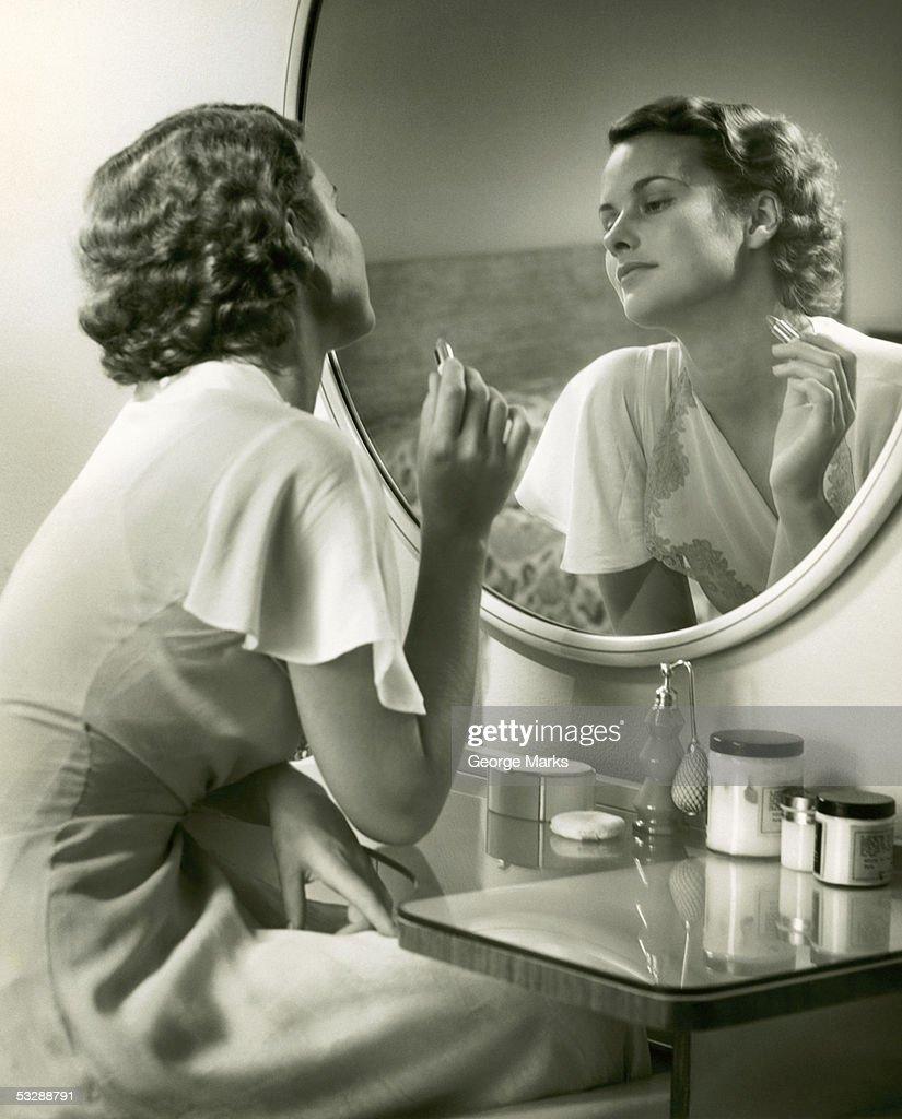 Woman sitting at vanity and staring at r : Stock Photo