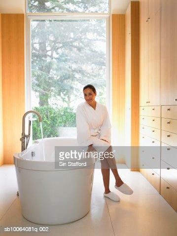 Woman sitting atop bath tub, portrait : Stock Photo