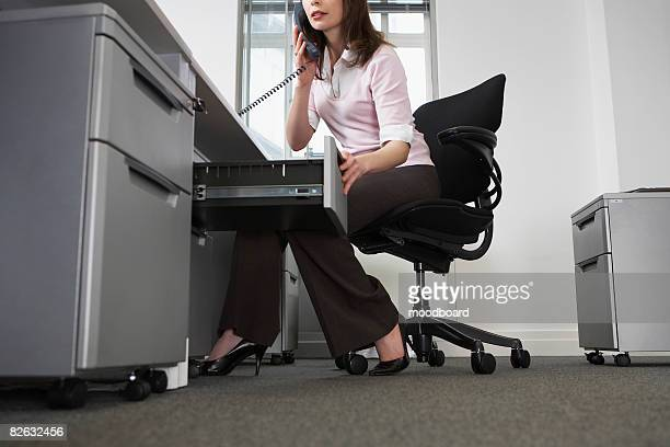 Woman sitting behind desk in office, using phone and opening drawer