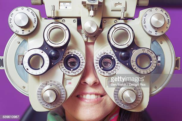 A Woman Sitting Behind Optometry Equipment In An Eye Examination