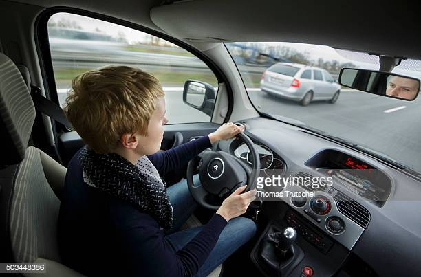 A woman sitting behind the steering wheel of a car and runs over a highway on December 22 2015 in Berlin Germany