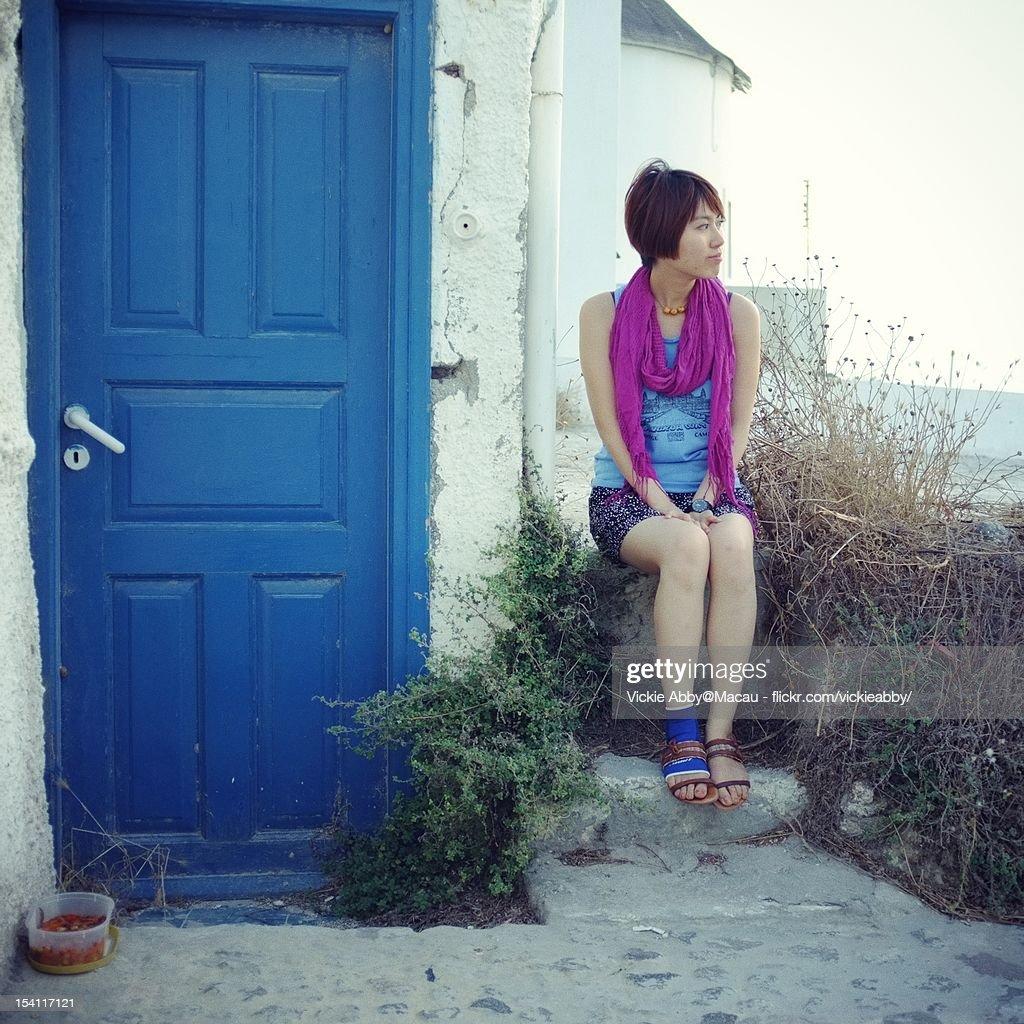Woman sitting beside blue door : Stock Photo
