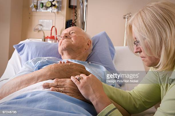 Woman sitting by a man's hospital bed