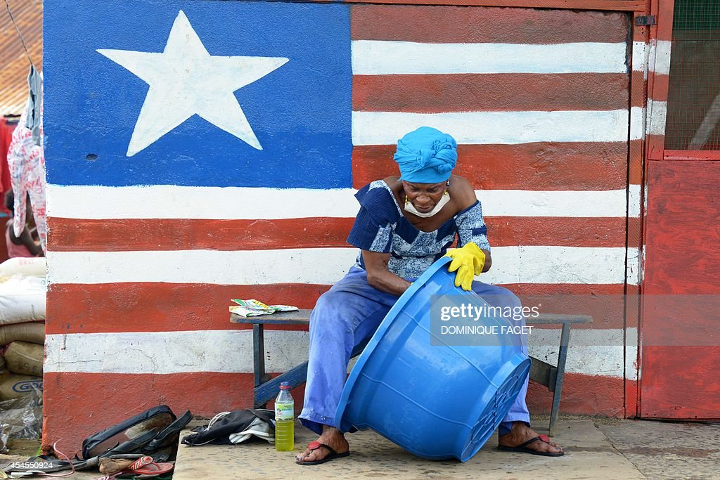 A woman sitting by a mural showing Liberia's national flag cleans a large basin in Monrovia on September 3, 2014. More than 1,900 people have died in the Ebola epidemic sweeping through West Africa, the head of the World Health Organization said on September 3. The latest toll represents a significant increase from the 1,552 deaths and 3,069 cases reported by the Geneva-based organization just days ago.