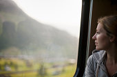 A woman sitting by a train window looking out at the landscape.