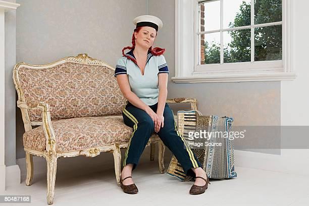 Frau sitzt mit Akkordeon
