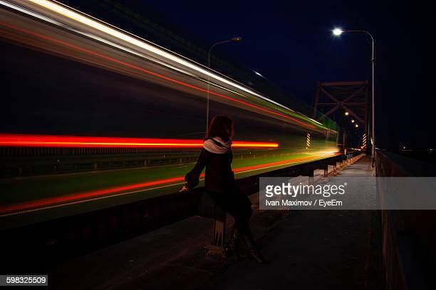 Woman Sitting By Bridge With Light Trails At Night