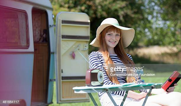 Woman sitting by caravan using digital tablet