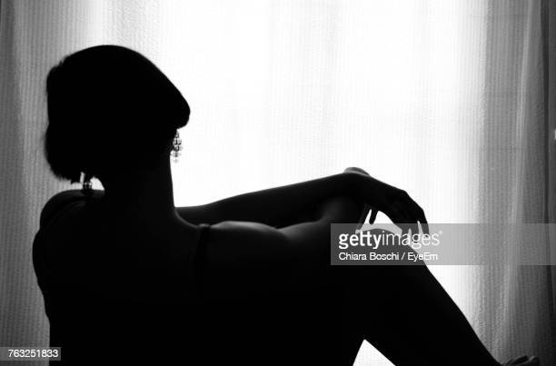 Woman Sitting By Curtain At Home