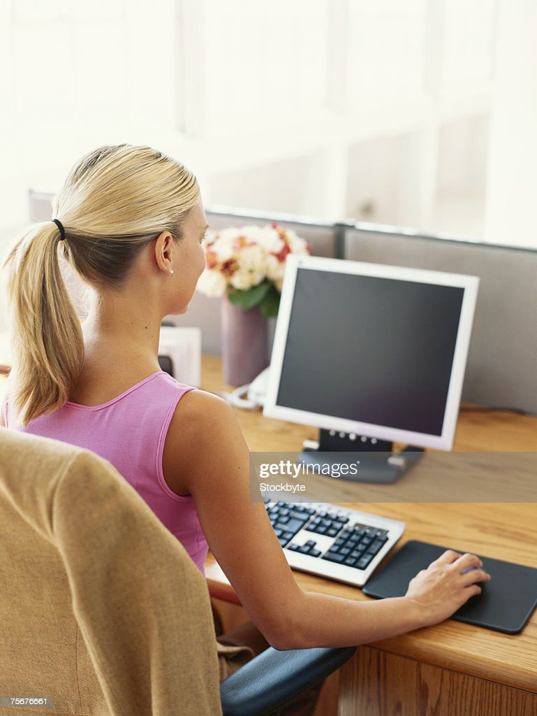 Woman sitting by desk using computer, rear view : Stock Photo