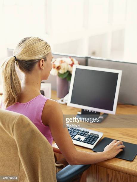 Woman sitting by desk using computer, rear view