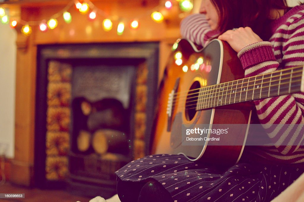 Woman sitting by fireplace with acoustic guitar : Stock Photo