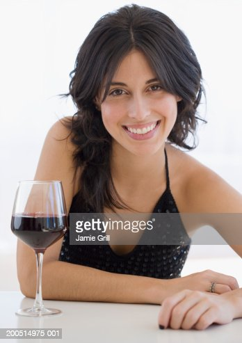 Woman sitting by glass of red wine, front view portrait. : Stock Photo