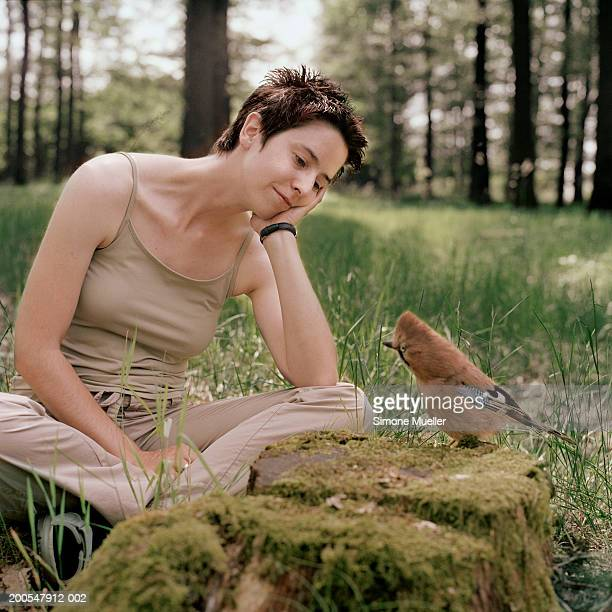 Woman sitting by jay on tree stump in forest