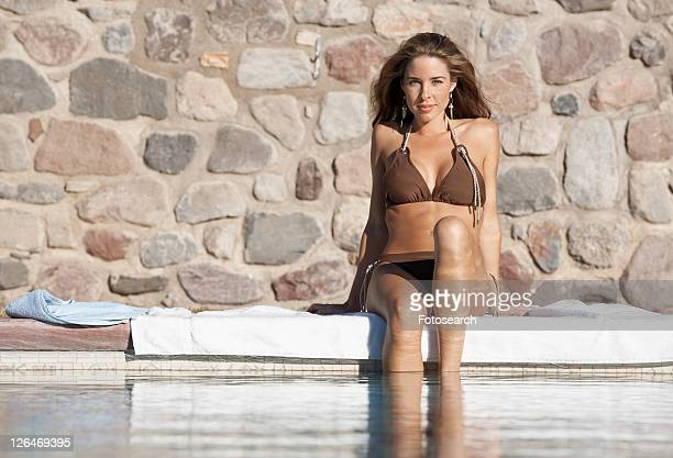 Woman sitting by pool with feet in water (portrait)
