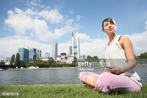 Woman Sitting by Riverbank : Stockfoto