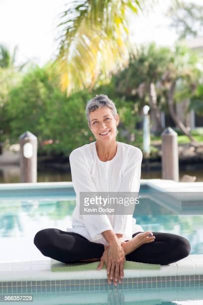 Woman sitting by still swimming pool