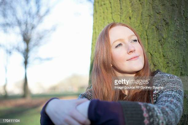Woman sitting by tree outdoors