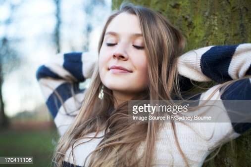 Woman sitting by tree outdoors : Stock Photo