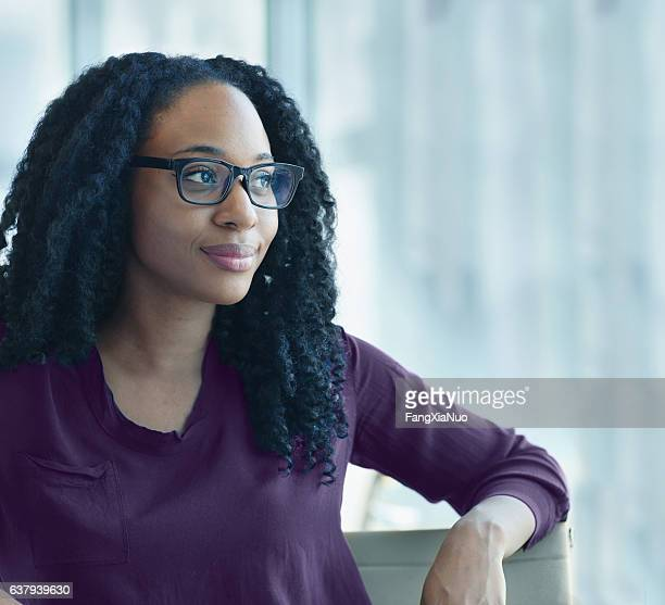 Woman sitting confidently in office looking out of window