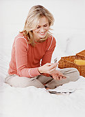 Woman Sitting Cross Legged on a Bed, Looking Down at Photographs