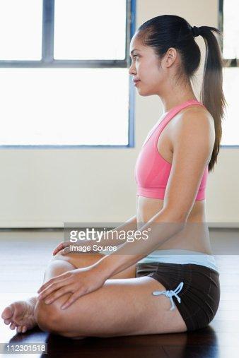 Woman sitting cross legged on floor : Stock Photo