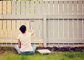 Woman sitting cross legged painting a fence