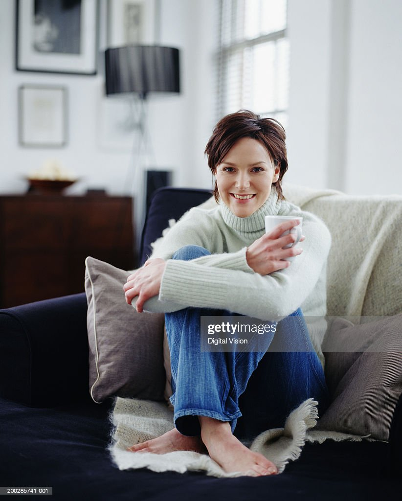 Woman sitting crossed legged on sofa, holding cup, smiling, portrait : Stock Photo