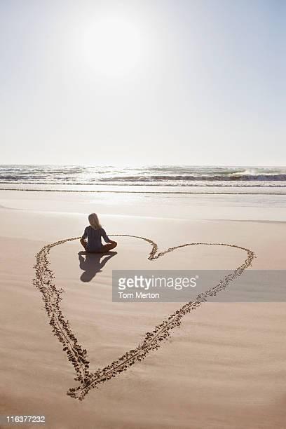 Femme assise Assis en tailleur de cœur sur la plage