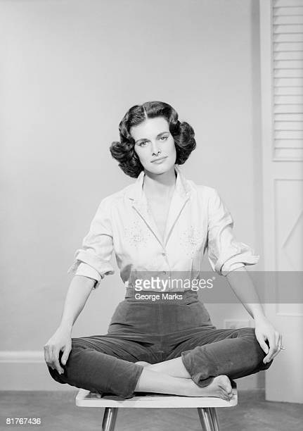 Woman sitting crosslegged on chair, portrait