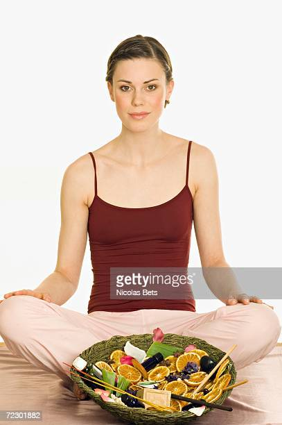 Woman sitting cross-legged, relaxation accessories in dish in front of her