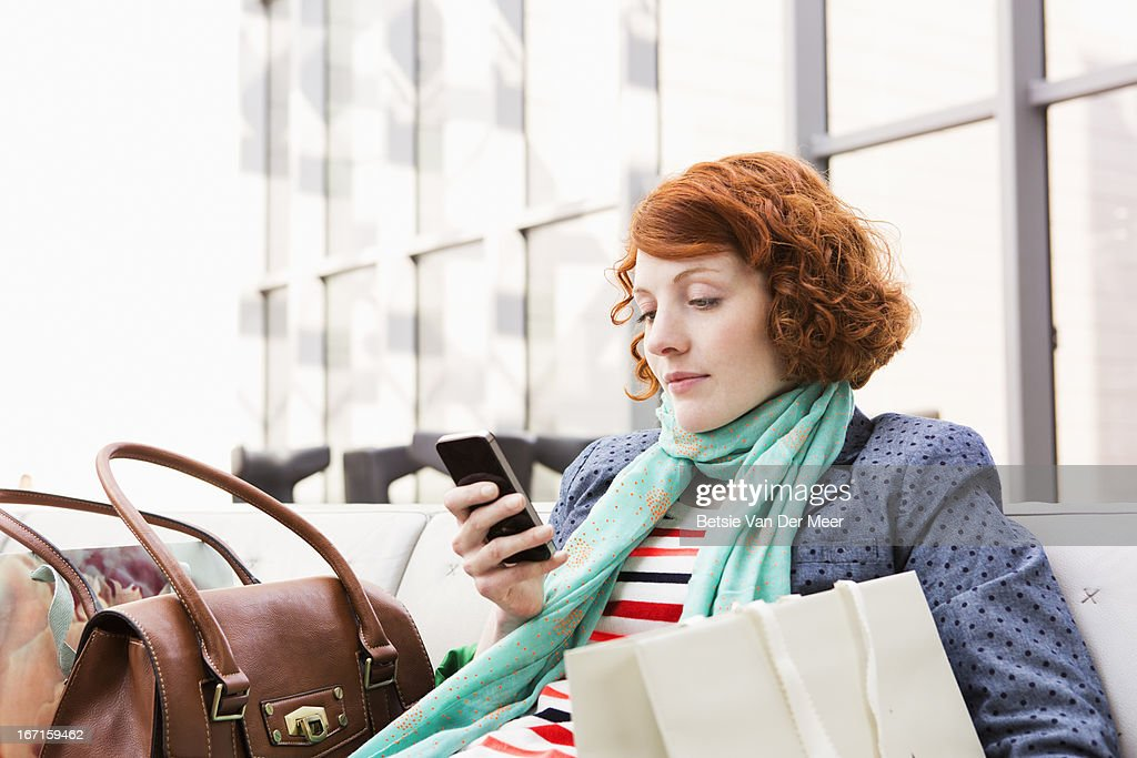 Woman sitting down checking messages. : Stock Photo