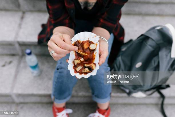 Woman Sitting Down On Steps Eating A Currywurst