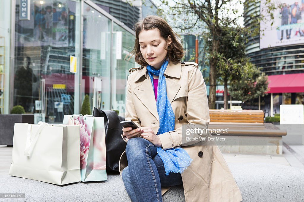 Woman sitting down with phone, in shopping street. : Stock Photo