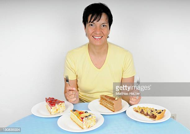 Woman sitting happily in front of four plates with cake
