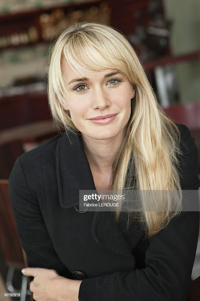 Woman sitting in a cafe and smiling : Stock Photo