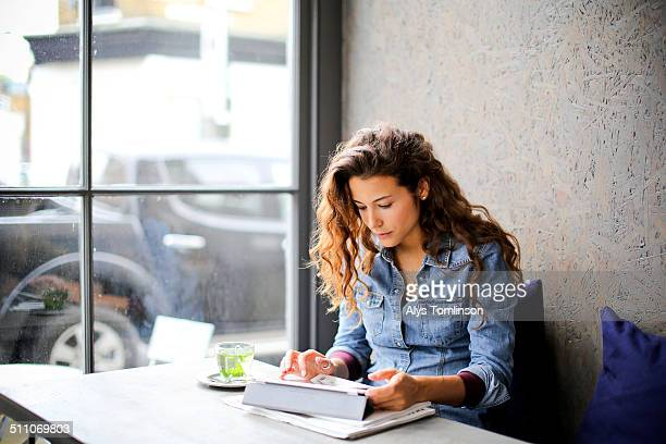 Woman Sitting in a Cafe Using a Tablet Computer