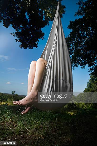 A woman sitting in a closed up hammock hanging from a tree, only legs visible