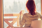 Woman sitting in a comfortable chair drinking coffee and looking through window at snow covered mountain.